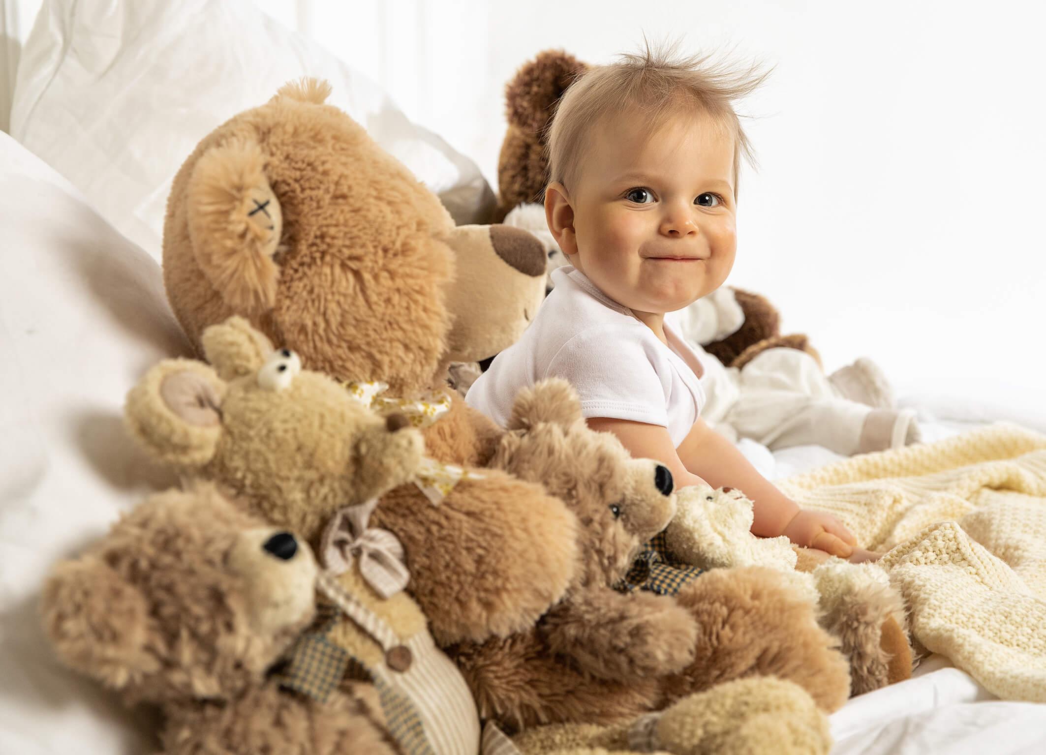 Babyfotos im Bett mit Teddybären