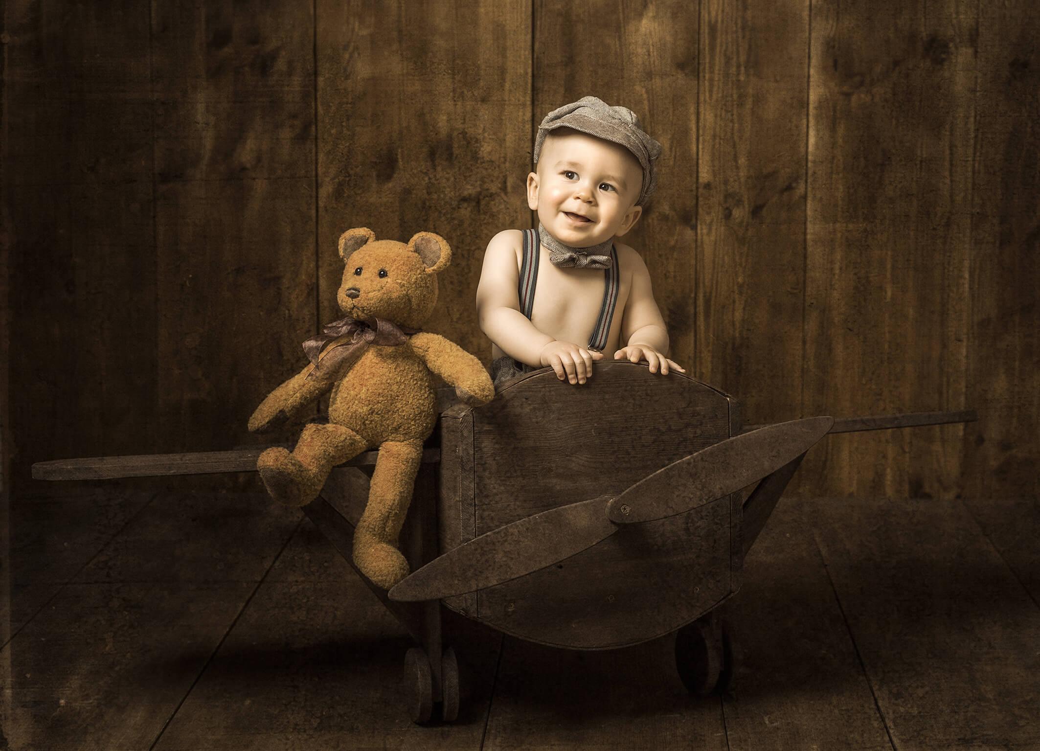 Babyfoto im Vintagestil mit Holzflieger